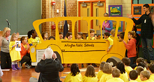 Children onstage in a play with a cardboard bus cutout.