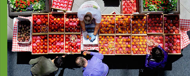 Overhead photograph of a farmrers market fruit stand full of peaches and produce.