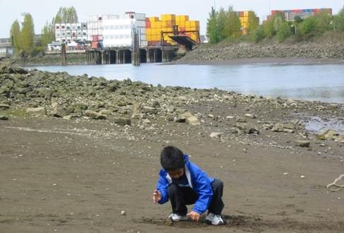 Kids playing in sand next to an urban waterway