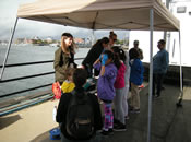 Students perform water quality experiments with EPA staff at the Canoemobile Event at the Charlestown Navy Yard. Students used USGS test kits to measure temperature, pH and turbidity.