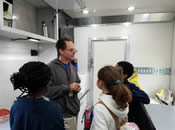 EPA Scientist discussing macroinvertebrates with students inside the Mobile Lab.