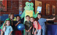 Group of kids smiling with lizard mascot
