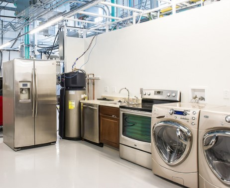 This is an image of durable goods at a store. Specifically shown are a refrigerator, washing machines and dryer, an oven with burners on top, and a kitchen sink.
