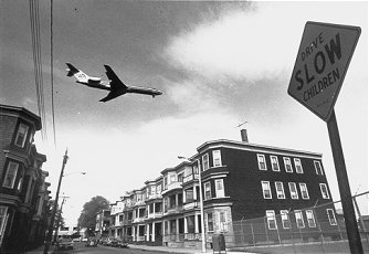 Black and white photo of a passenger airplane flying over a city.