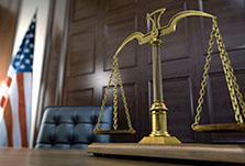 stock photo of judges bench with justice scales on desk and U.S. Flag in background