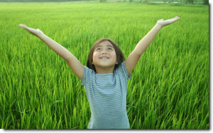 girl standing in green grass, smiling while looking up and raising her arms