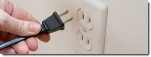 hand plugging a power cord into an outlet