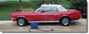 red car being washed in a driveway