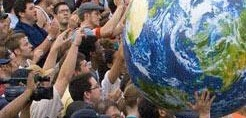 Crowd holding a large planet earth