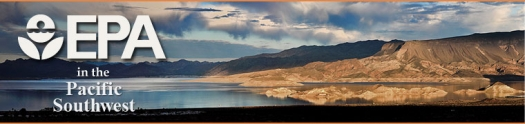 Lake shore with desert landscape, low mountain ranges, and rainclouds
