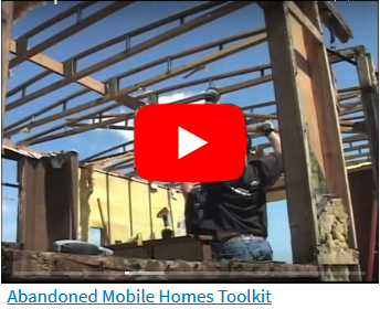 Workers desconstructing a mobile home - exposed rafters with now roof - sky visible