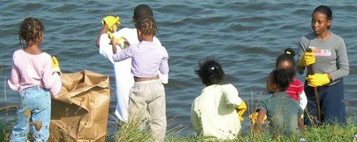 Children near a lake picking up trash