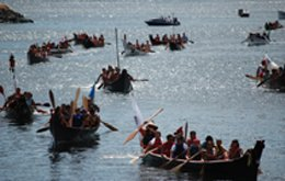 Photograph of ceremonial canoes on the water, depicting the gathering of Salish Coast people who travel through the waterways of the Salish Sea to annually to celebrate their connection to salmon, water and each other.