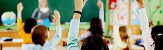 Students in a classroom with their hands raised