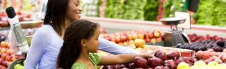 Mother and daughter looking at fruit in a grocery store
