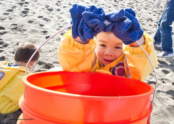 Photo of kid with bucket cleaning up at the beach