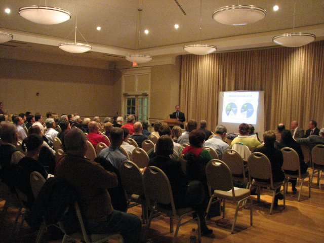 This image shows a public meeting that took place in Williamsburg, Virginia. The image shows the backs of the audience, the speaker at a podium and slides projected onto a screen next to the speaker.