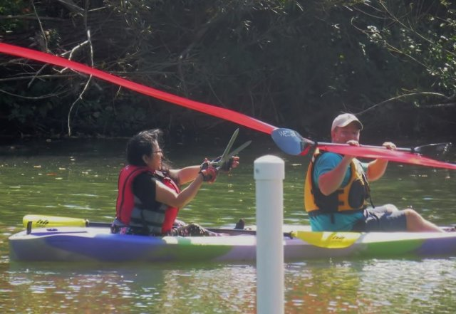Young woman in a tandem kayak reaches out with ceremonial scissors to cut the ribbon and open the first handicap accessible boat launch in Indiana.