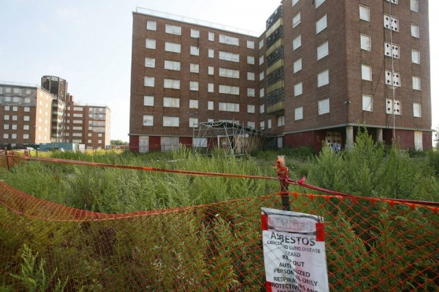 photo of pre demolished kensington towers buildings with focus on asbestos warning sign