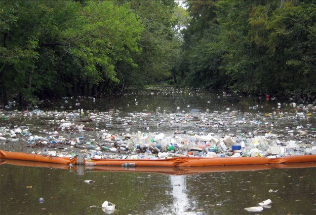 Floating orange inflatable plastic boom holding back most floating trash on a river