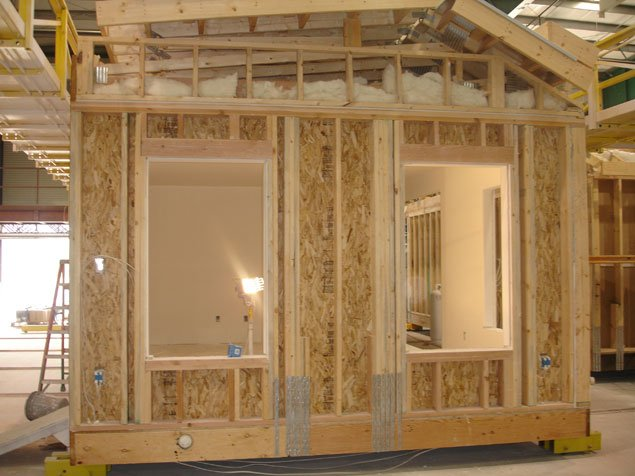 Closeup of modular home under construction on factory floor.