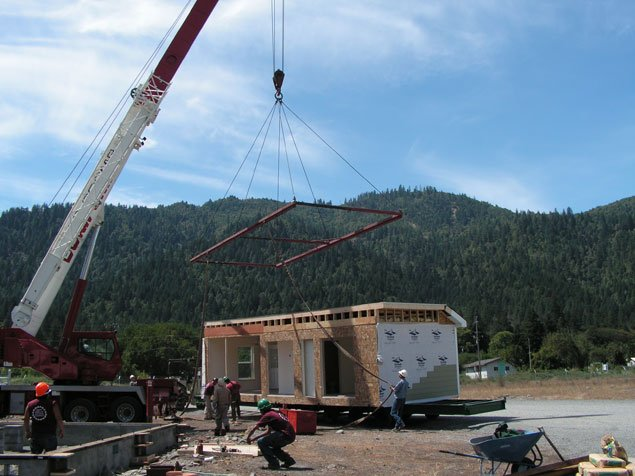 Manufactured home being lifted off of a flatbed with a crane for installation on site.