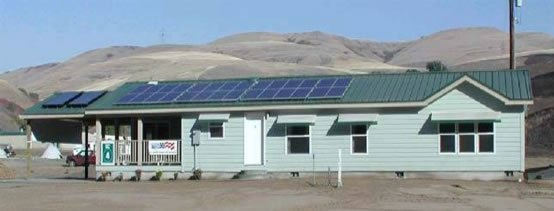 Factory constructed home on site with solar panels and awnings over windows.