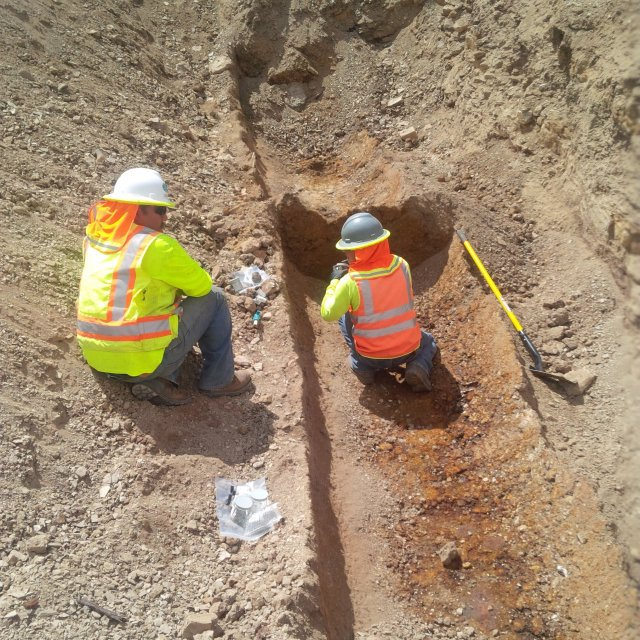 Workers taking samples from exposed trench.