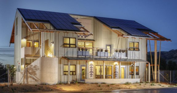 Home like two story building with solar panels and tribal exterior decor.