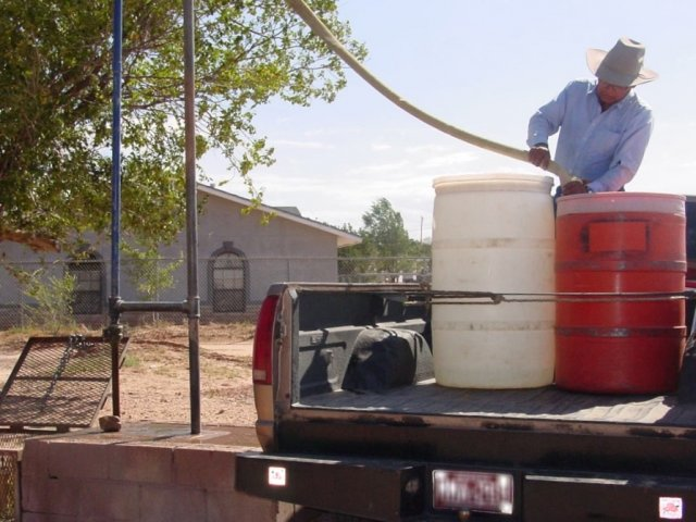 Man filling up water drums at water hauling station in Ganado