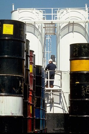 A man climbing a ladder between two large barrels of chemicals