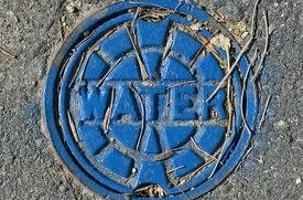 A blue manhole cover with the word water stamped on it.