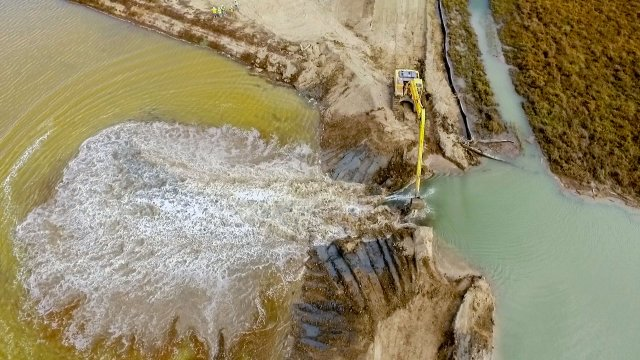 Aerial view looking down on an earthmover digging a breach in the levee at sears point. Water is pouring through the breach from right to left and flooding a pool.