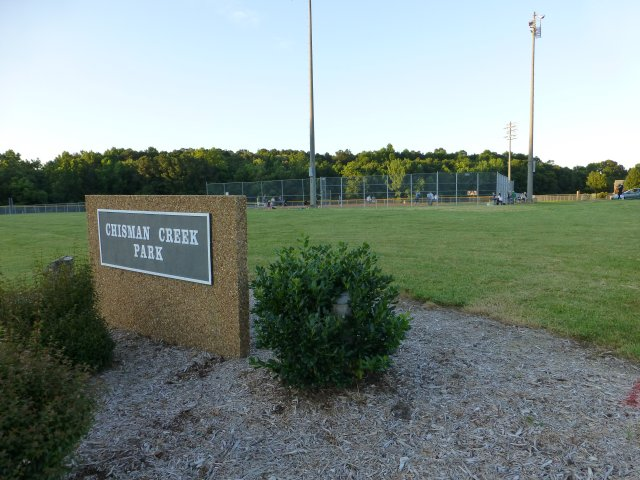The Chisman Creek Park sign and baseball field in the background