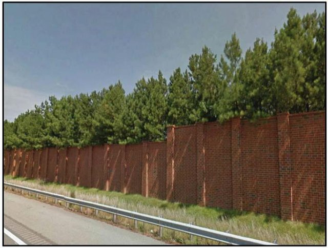 Photo shows a large brick wall with trees and vegetation extending over the top. The wall and vegetation is lining the side of a highway.