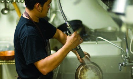 Man using the pre-rinse spray valve