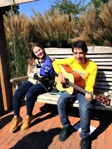 Two kids sitting on a bench playing guitars