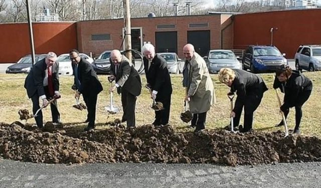 Officials scoop shovels of dirt as part of the groundbreaking ceremony for the Reading wastewater plant.