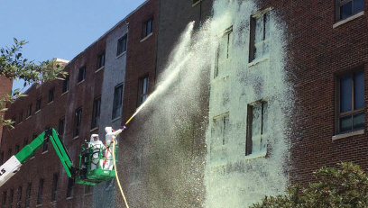 Firefighter applying a chelating agent to a building
