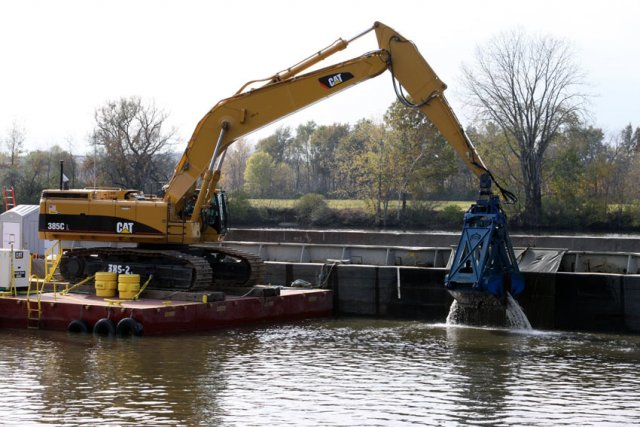 Dredging in the Upper Hudson River was conducted between 2009-2015. Workers use excavators with environmental clamshell buckets mounted on flat, anchored platforms to dredge the river. The PCB-contaminated sediment was emptied onto 35-foot-wide, 195-foot-long floating barges.
