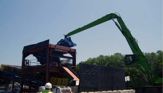 Workers at the processing facility used excavators with environmental clamshell buckets to load the contaminated sediment and debris onto a trommel which began the process of separating the material.