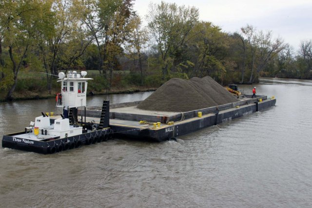 After an area has been dredged of contaminated sediment to the EPA's standards, clean backfill was transported on a barge by a tug boat. The backfill replaced dredged sediment and maintained the natural contours of the riverbed.