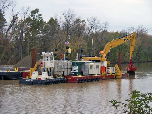 Workers used excavators with environmental clamshell buckets mounted on flat, anchored platforms to place backfill on top of the previously dredged area, returning the riverbed to its natural state.