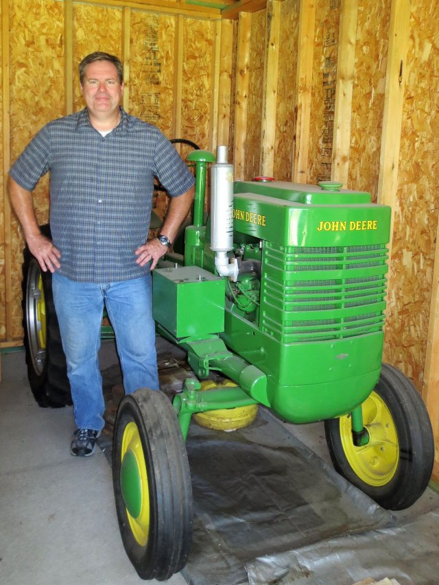 Robert Weber standing in front of an antique tractor on his family farm
