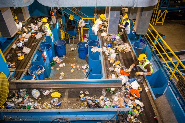 This is a photo of workers at a recycling center sorting materials that can and can't be recycled as they pass by on a conveyor belt.