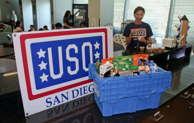 This is a picture of a donation box next to a large red, white and blue USO San Diego sign