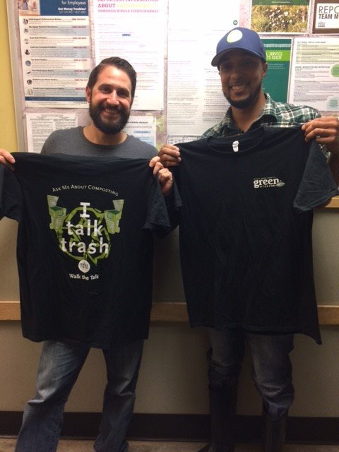 This is a picture of two Whole Foods employees holding up shirts that say I talk trash, Ask me about composting and walk the talk.