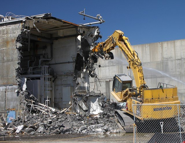 This is a picture of a partially demolished building. There also is debris on the ground in front of the part of the building that is demolished, and a yellow crane is picking up some debris.