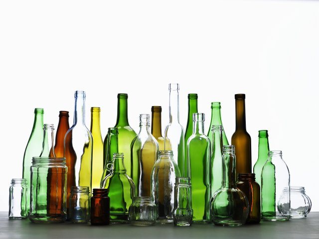 This is a picture of glass bottles of different sizes, shapes, and colors. Some are transparent while others are green, yellow and brown.