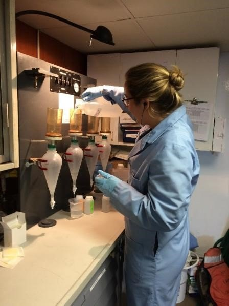 A scientist onboard the R/V Lake Guardian filtering raw water samples in the wet laboratory.
